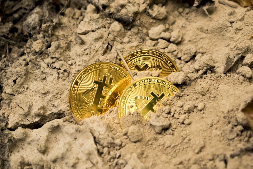 three Bitcoins on soil