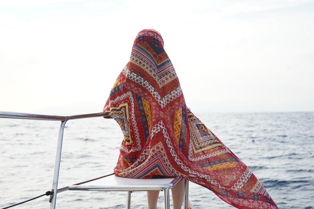 woman sitting on chair beside sea