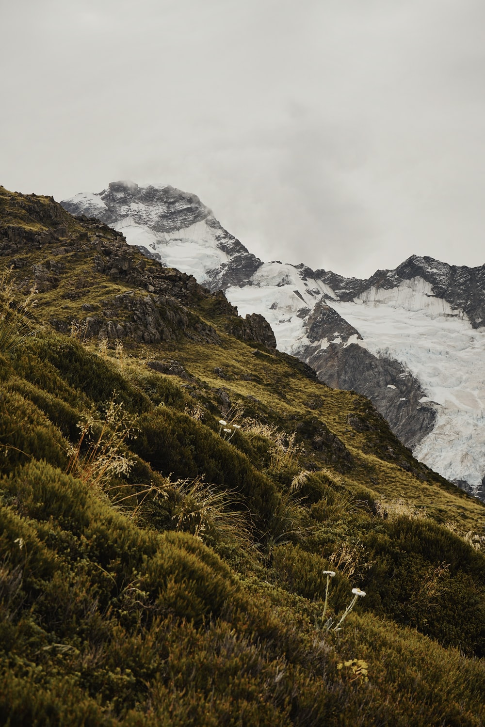green mountains and gray mountain covered with snow