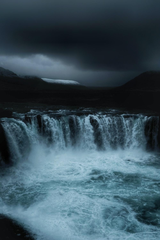 running waterfalls under grey clouds