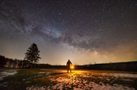 person holding torch in middle of open field under starry sky