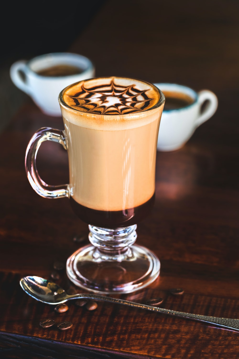 food photography of coffee latte next to stainless steel spoon