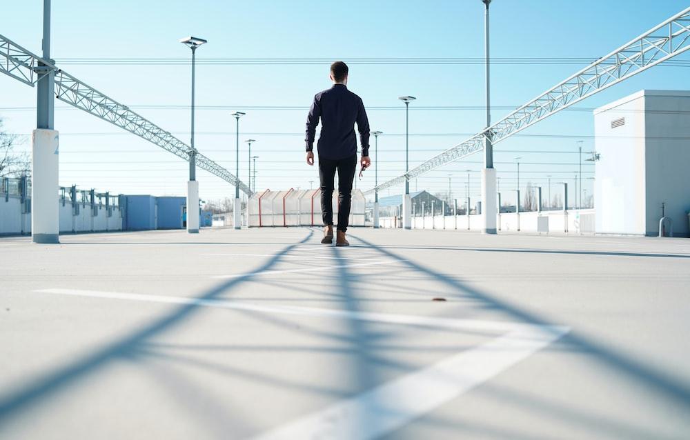 man standing on gray surface near metal frames