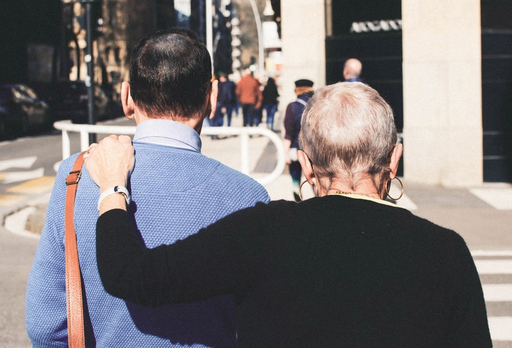 woman put her hand on man's shoulder while walking during daytime