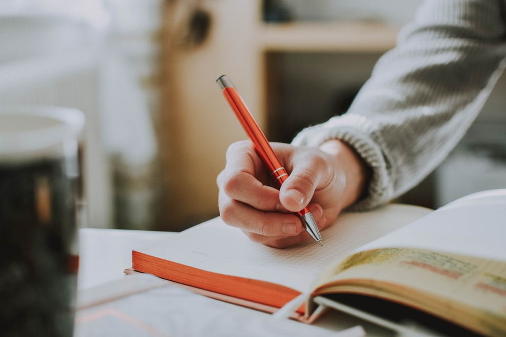 person holding on red pen while writing on book