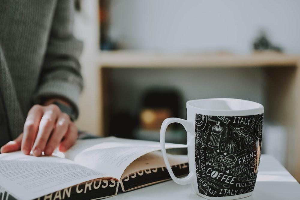shallow focus photo of white and black ceramic mug