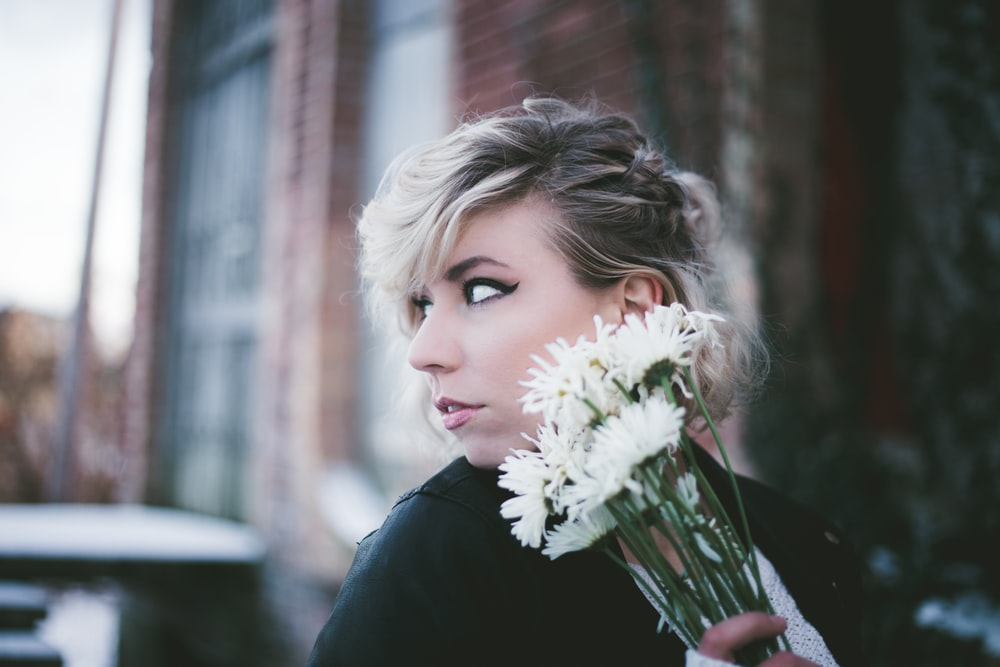 woman holding white mums flowers