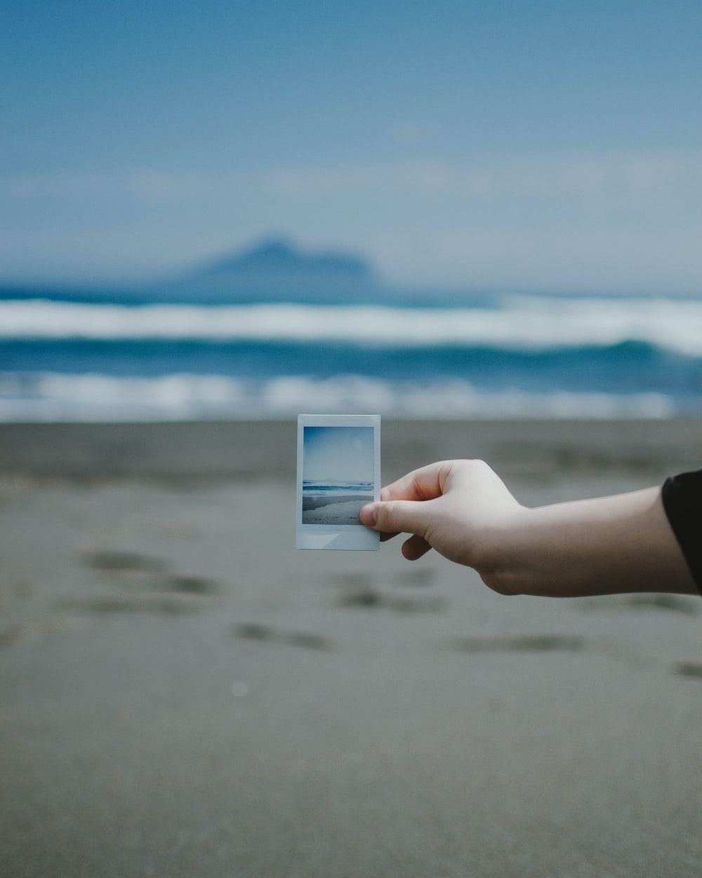 person holds photo of ocean at the beach