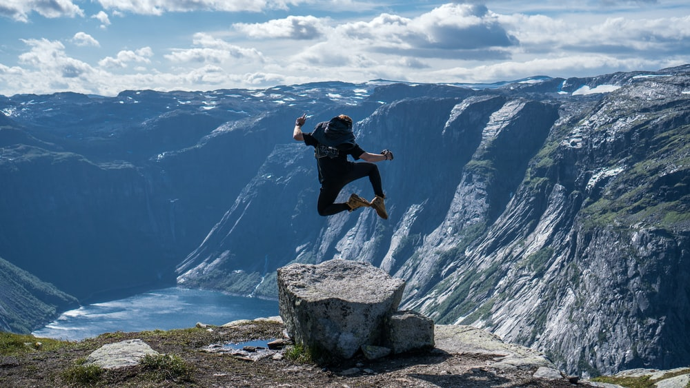 person jumping at the peak of mountain