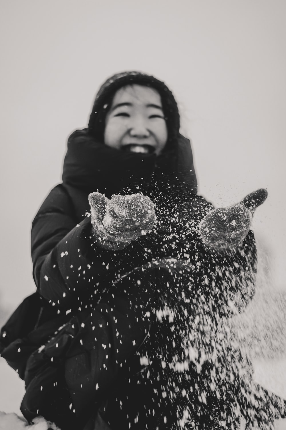 grayscale photography of woman playing with snow
