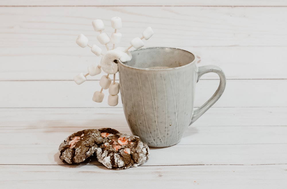 gray ceramic mug on white wooden surface