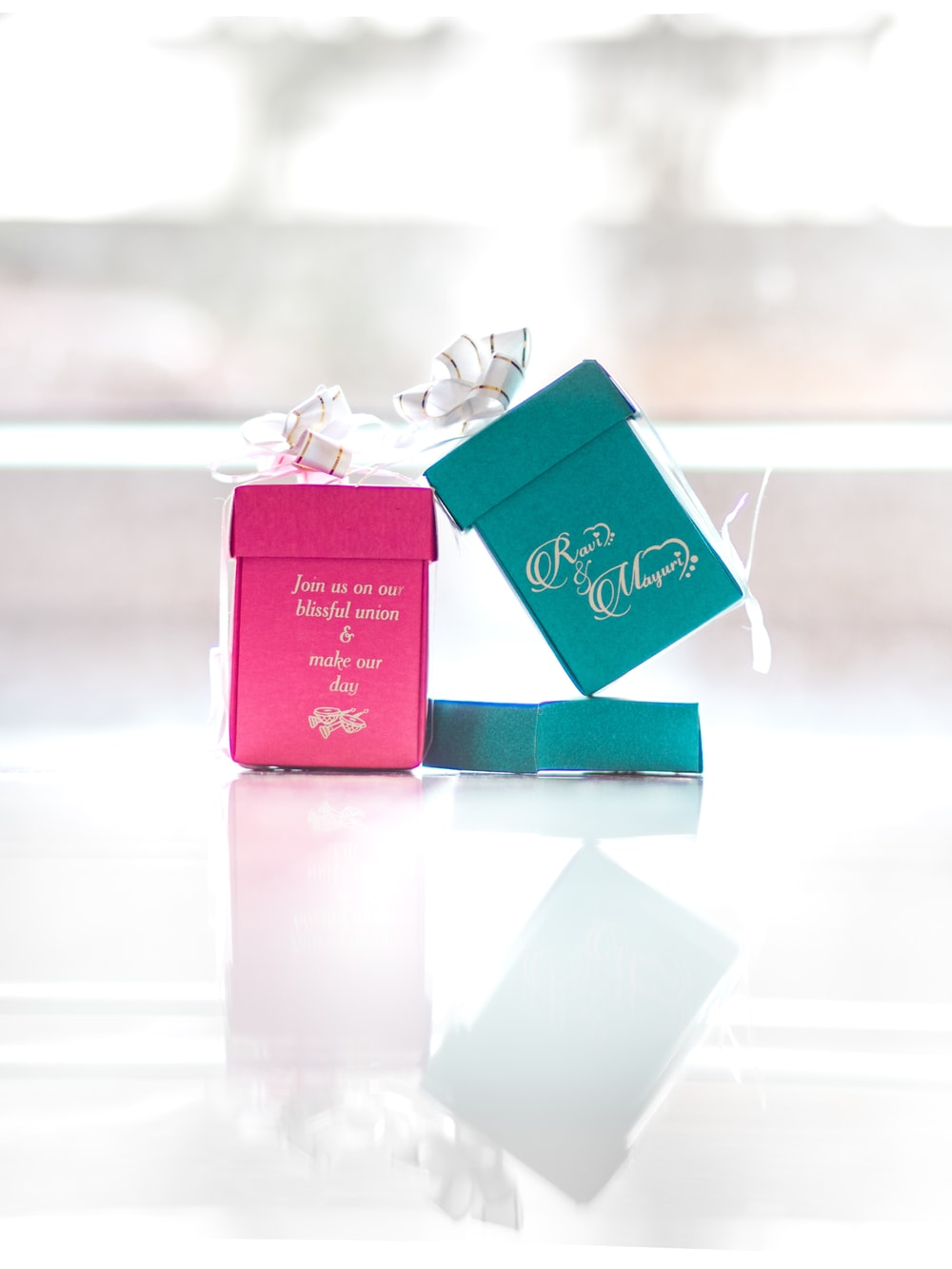 two pink and teal ring boxes