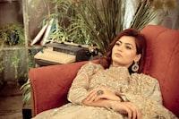 woman lying on red sofa near green leaf plant