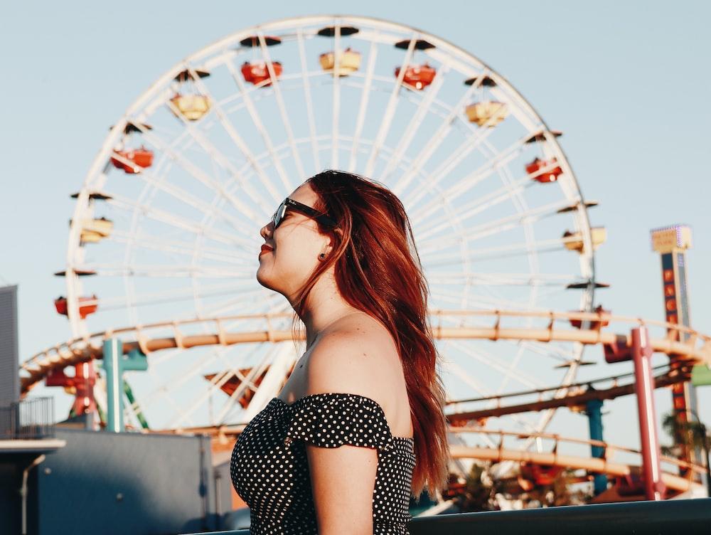 woman standing near ferris wheel