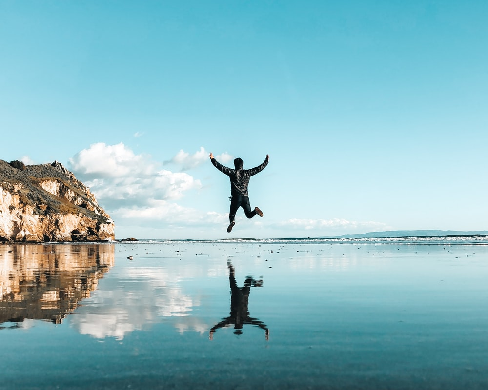 man jumping on top of body of water under blue sky