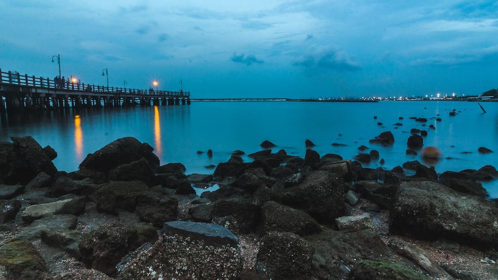 gray rocks beside calm body of water and bridge