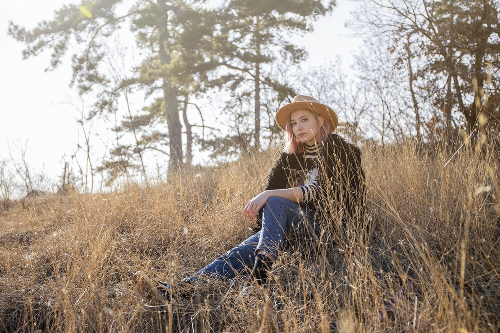 woman wearing brown sun hat, black jacket, and blue jeans sitting on slope of grass during daytime