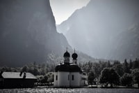 grayscale photo of chapel near body of water surrounded with mountains
