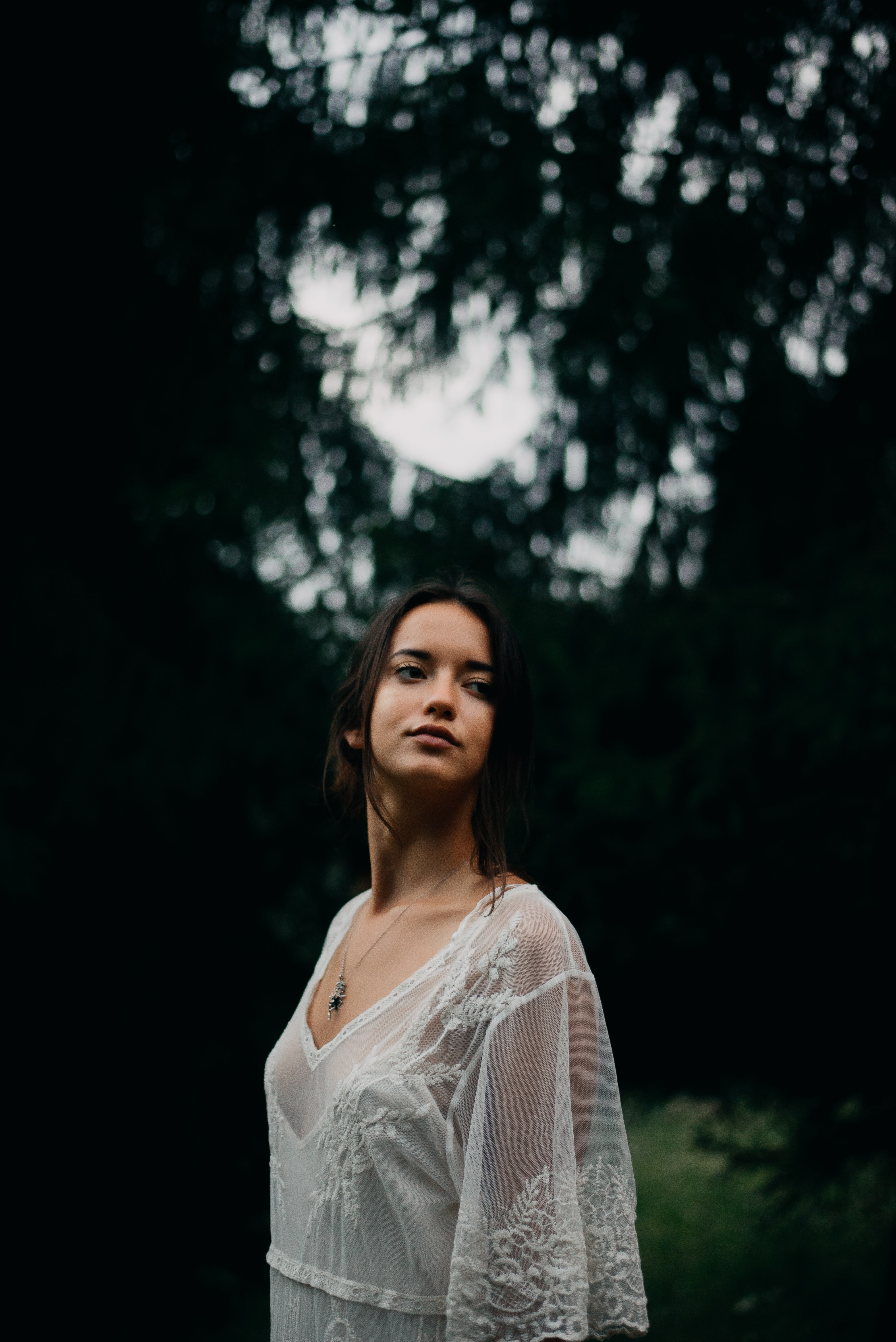 selective focus photography of woman standing near trees wearing white sheer top