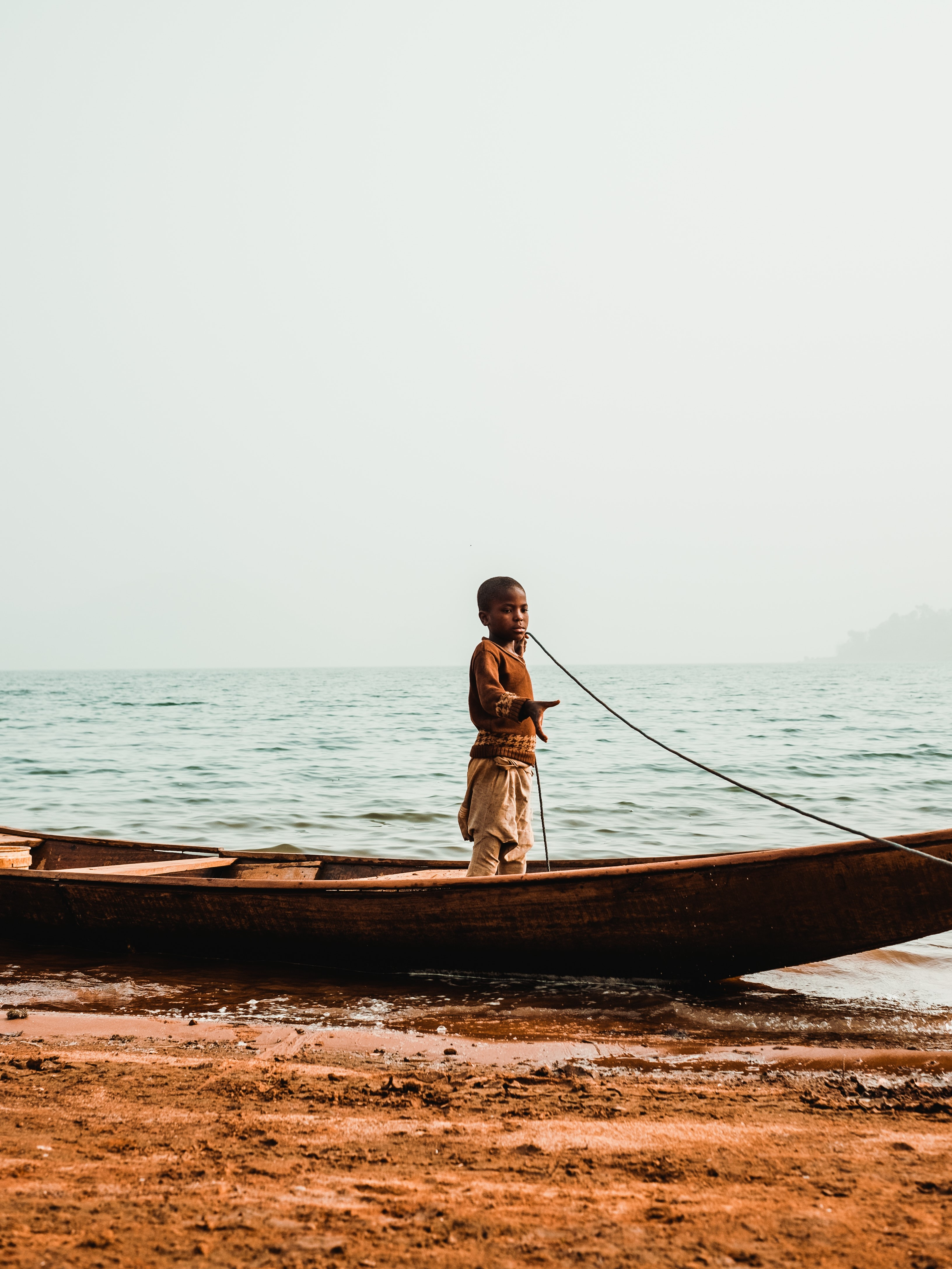 boy standing in boat while holding rope