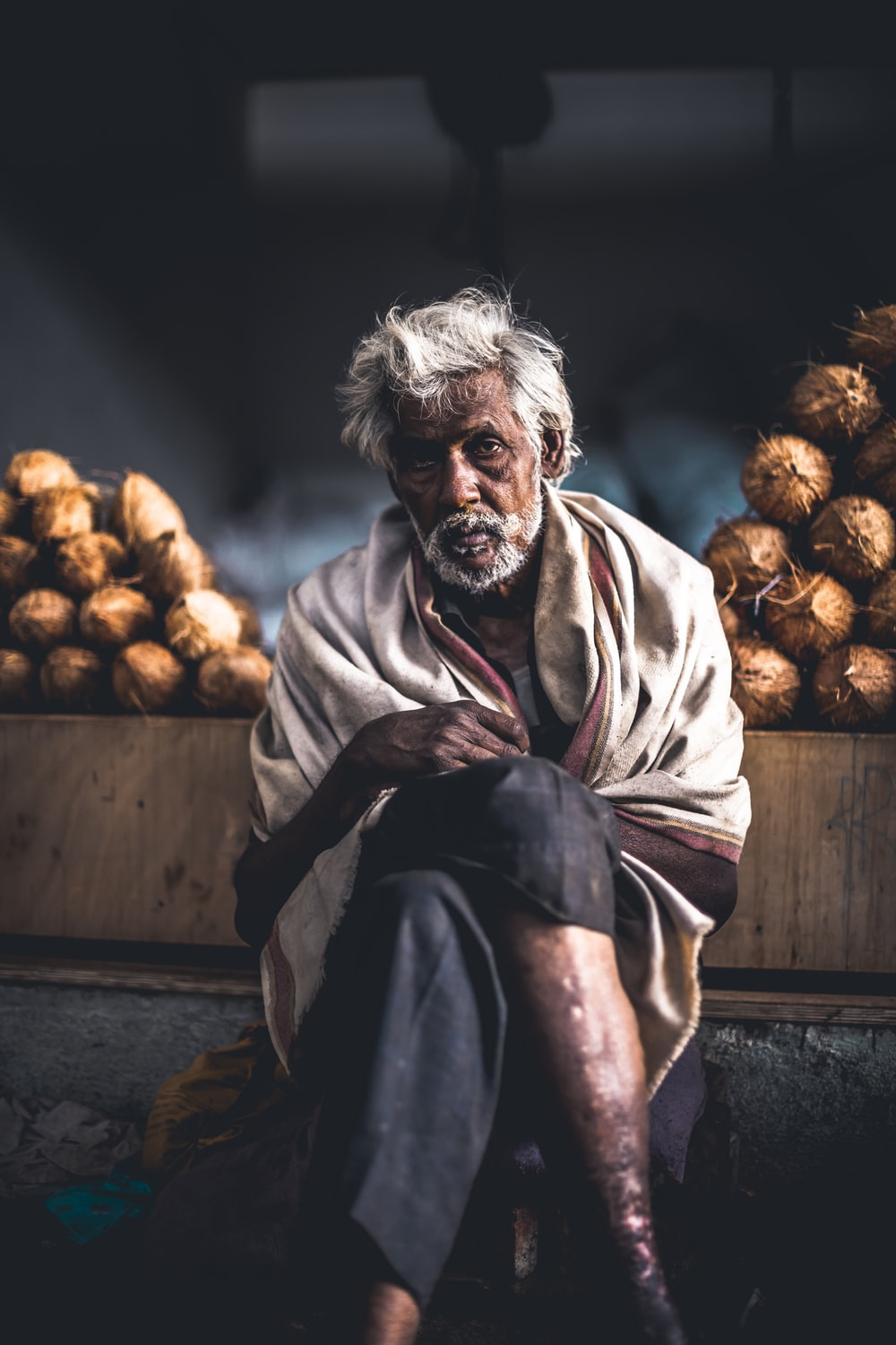 man sitting beside coconut stand