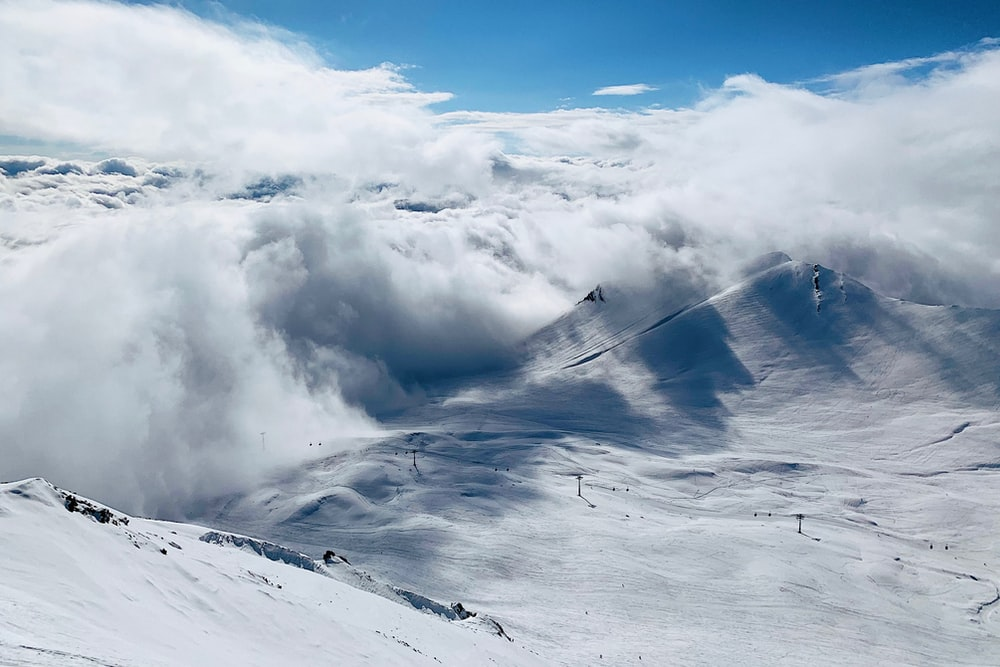white mountain covered with snow with clouds