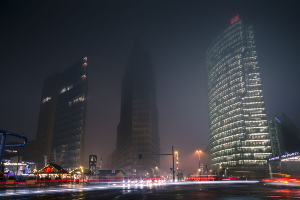 three gray high-rise buildings at night time