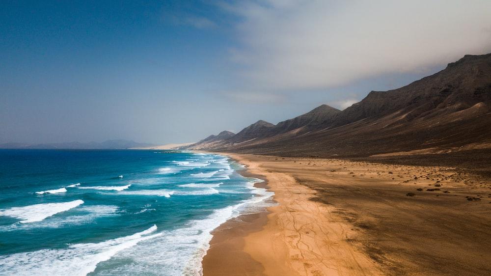 mountain beside sea at daytime
