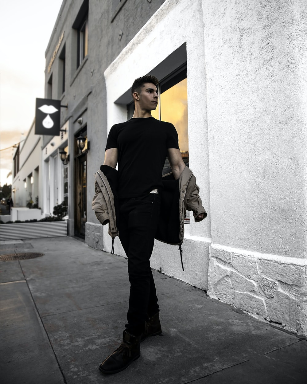man in black shirt and gray pants leaning on wall