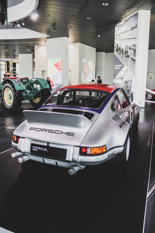 silver Porsche vehicle parked inside building near green vehicle