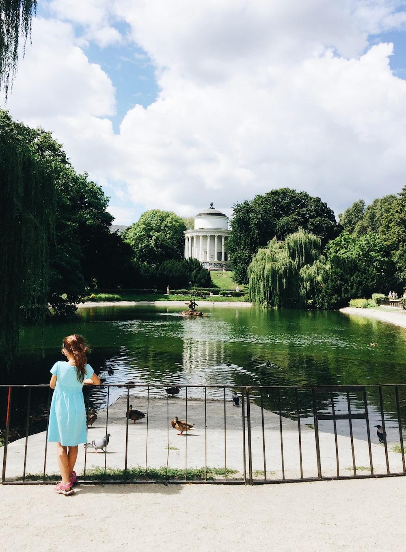 girl standing near pond