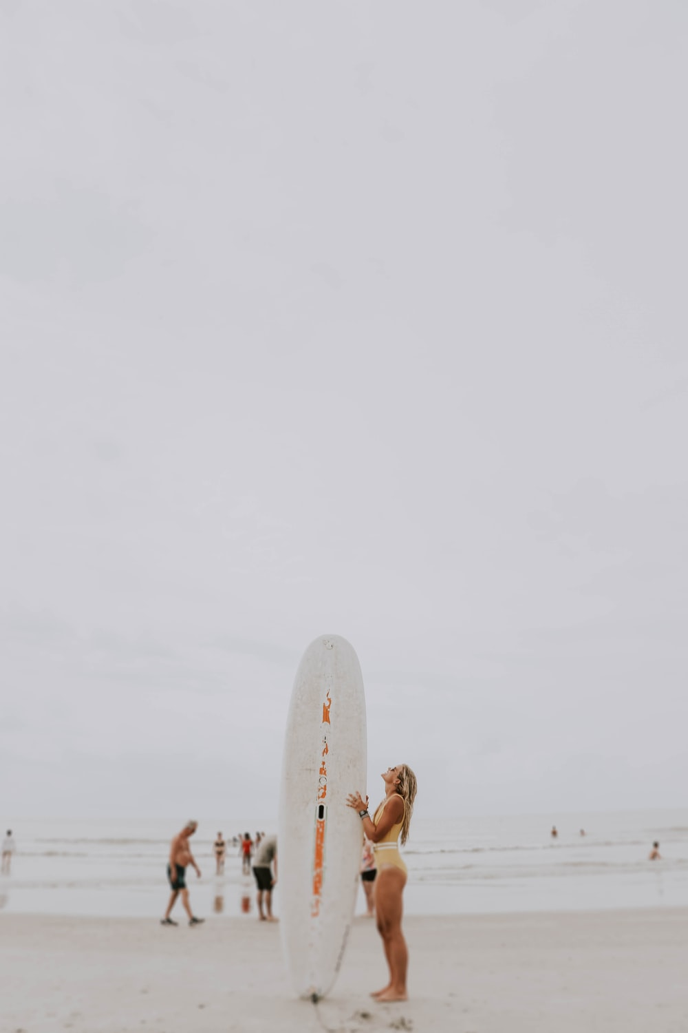 woman standing and holding surfboard near seashore