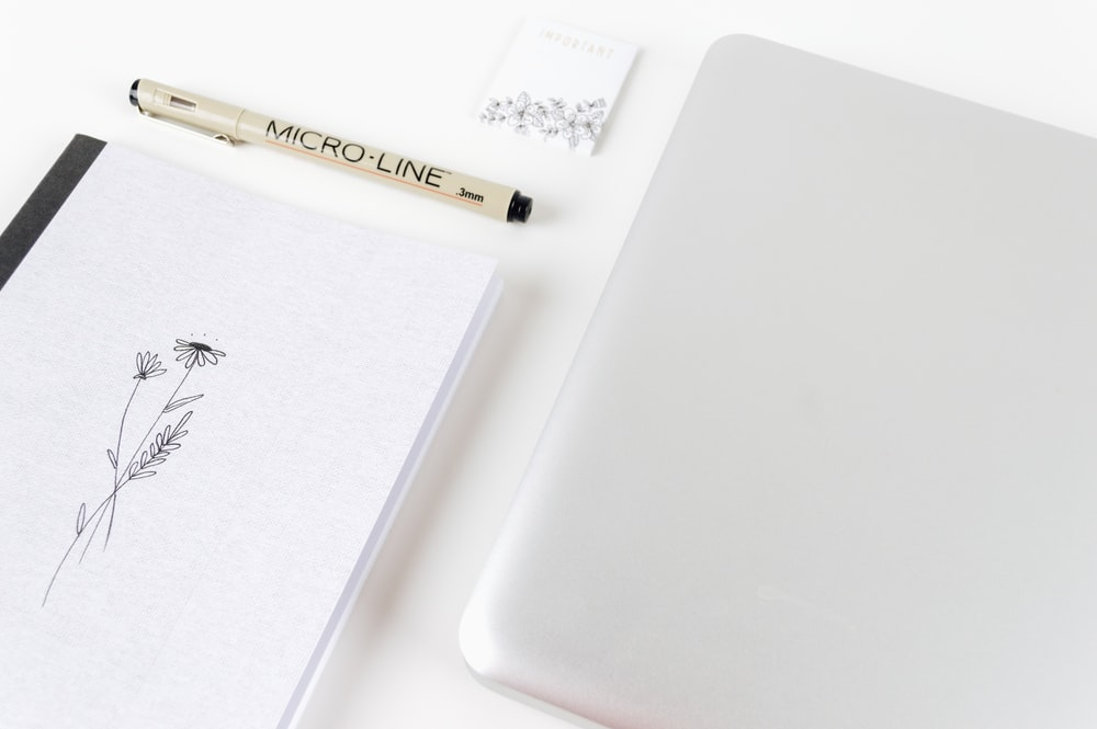 white laptop computer beside micro line pen