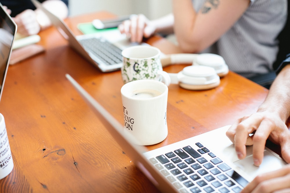 two ceramic mugs on table and two person using laptop