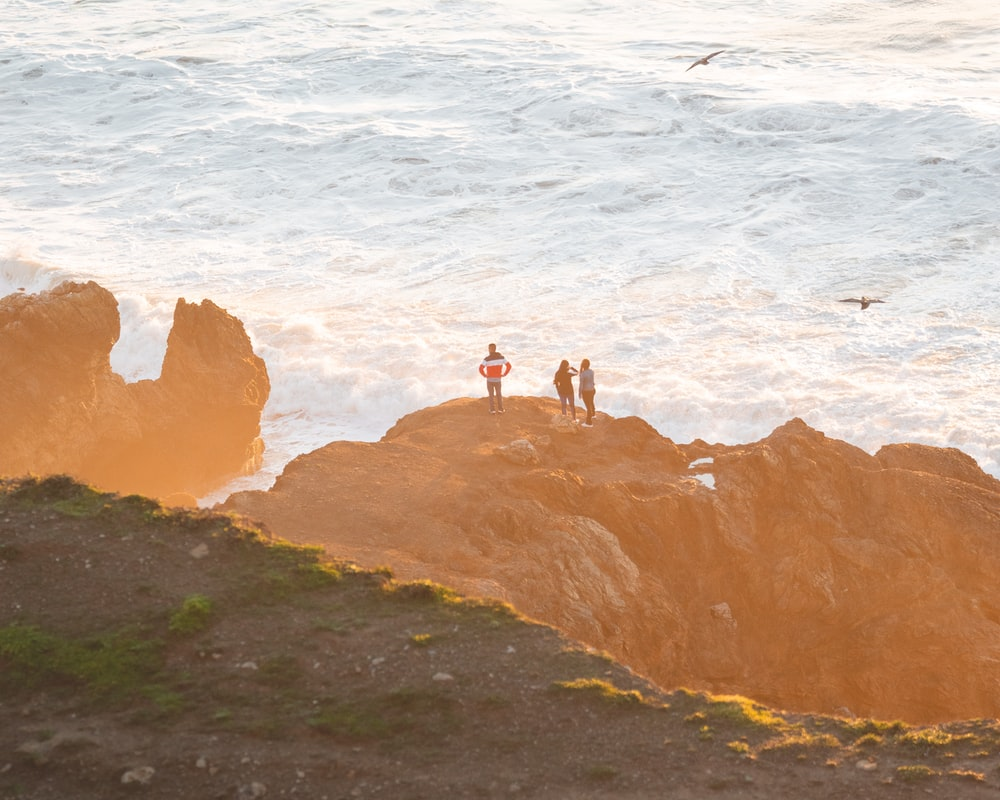 three person standing on cliff near ocean