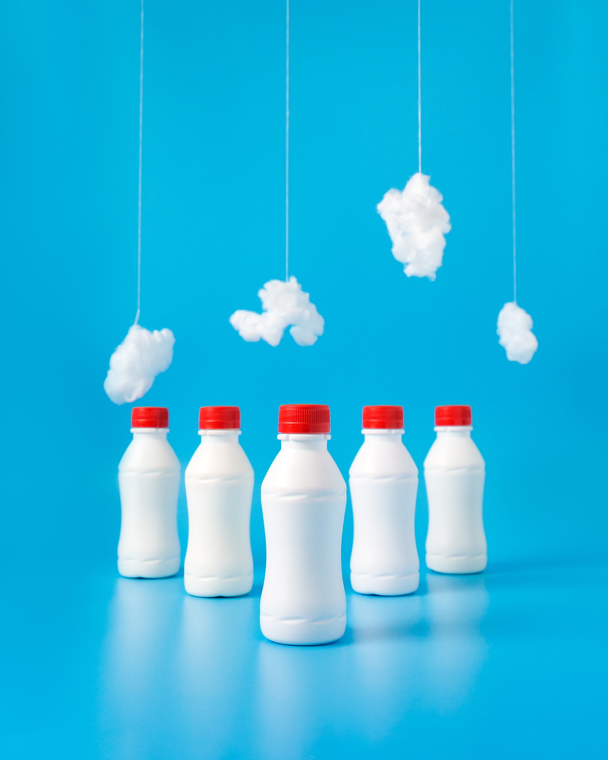 five white plastic bottles on blue surface
