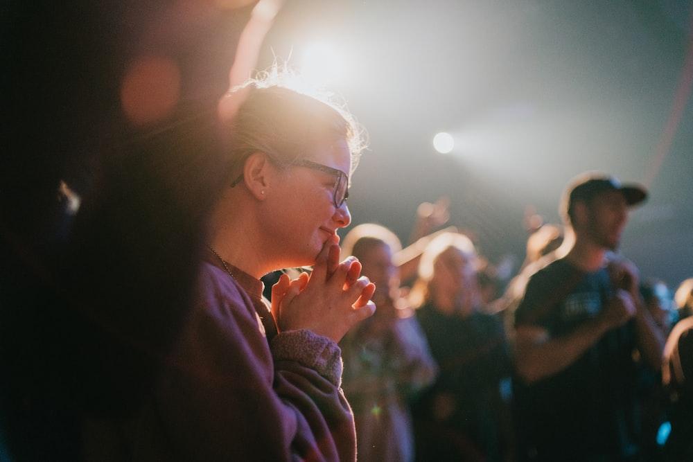 selective focus photography of woman praying