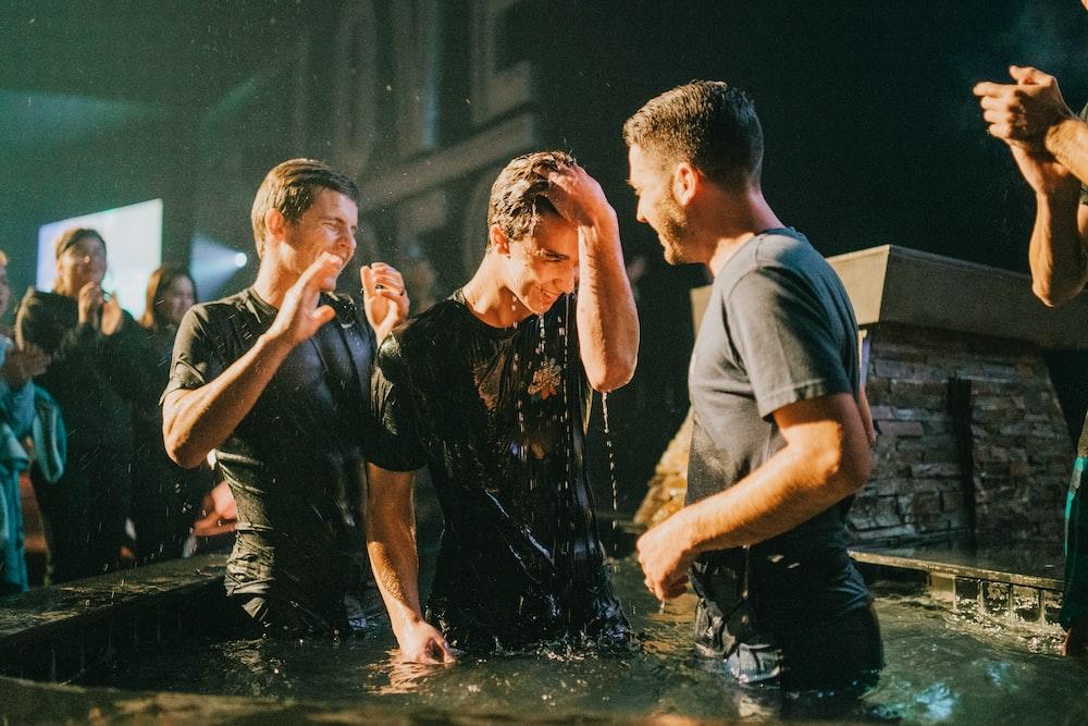three men standing on black tub full of water