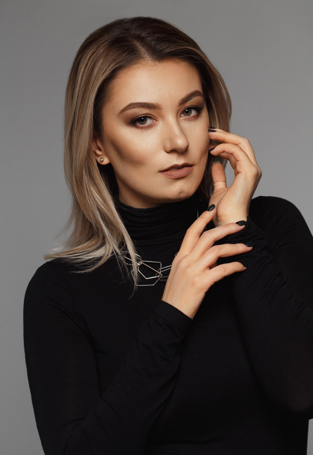selective focus photography of woman in black turtle-neck long-sleeved shirt