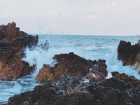 sea waves crashing on brown rock