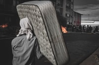 person carrying white mattress