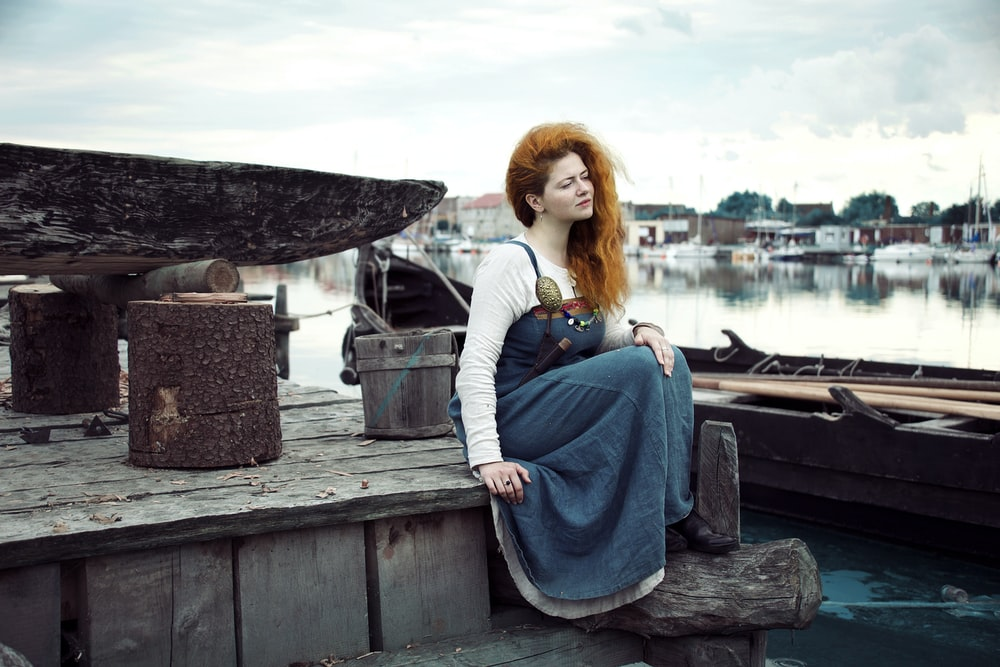 woman in blue dress sitting on brown dock
