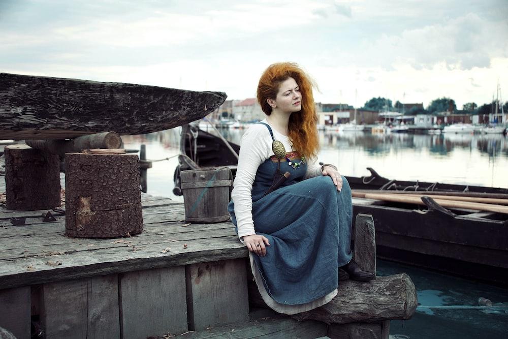 woman in blue dress sitting on brown dock
