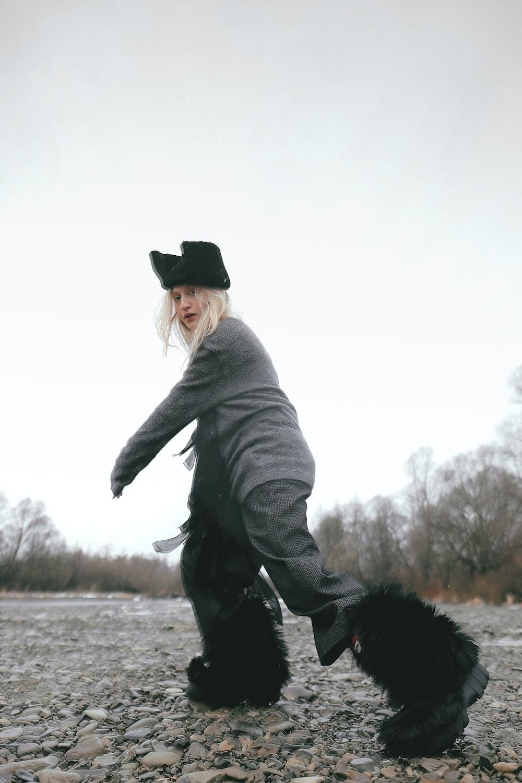 woman in gray top walking on rocky road