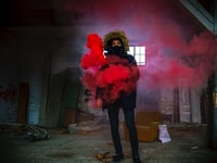 man in black coat with red smoke