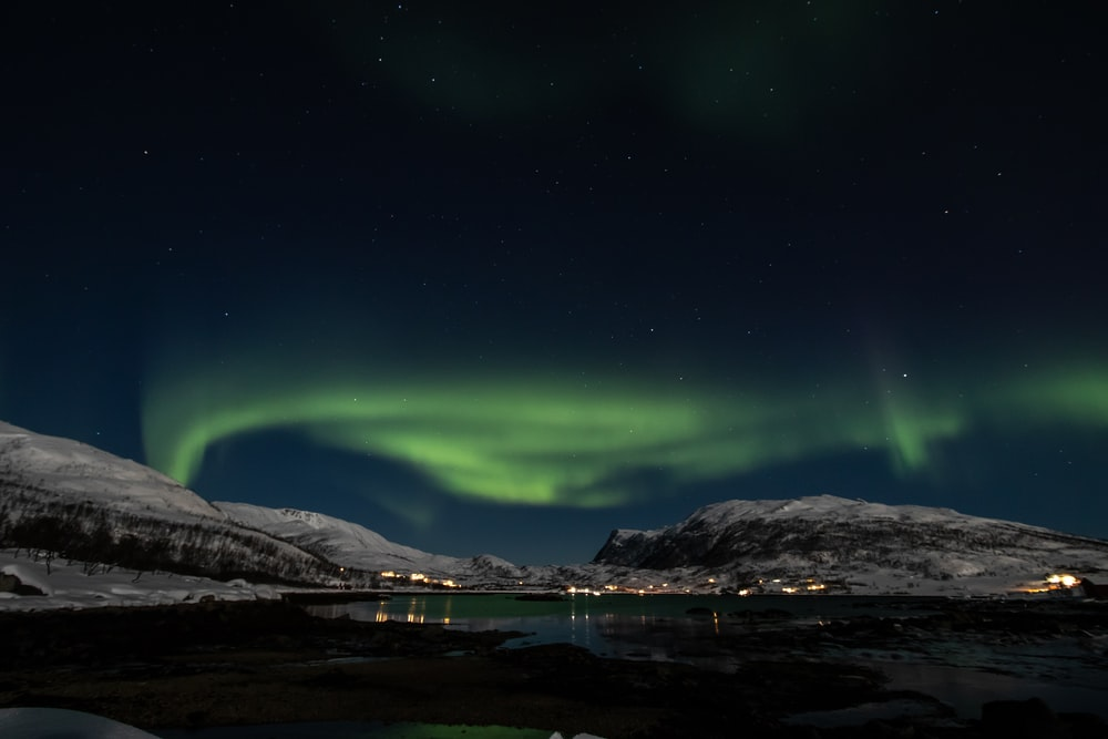 aurora borealis above mountain and body of water