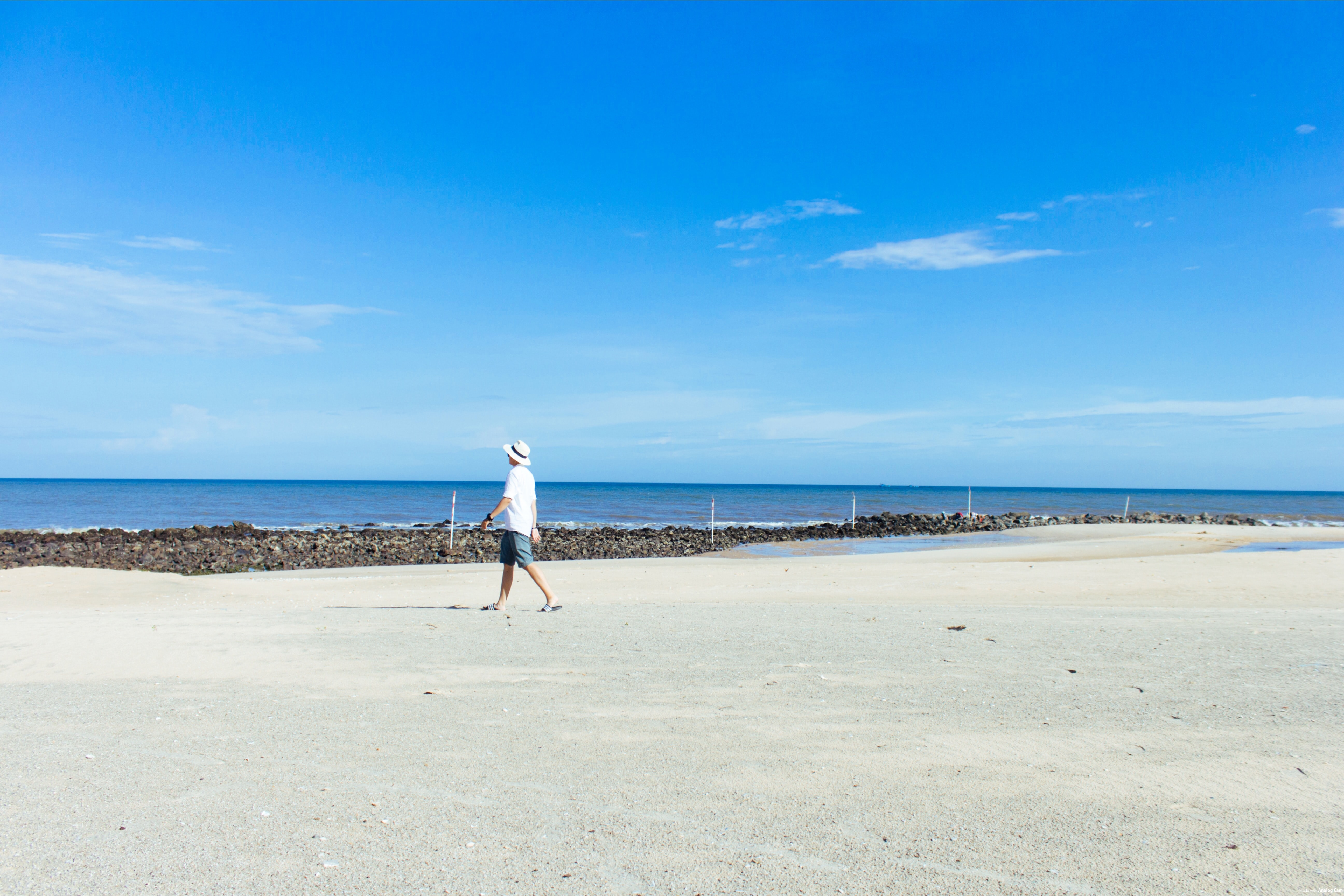 man walking on seashore under blue sky
