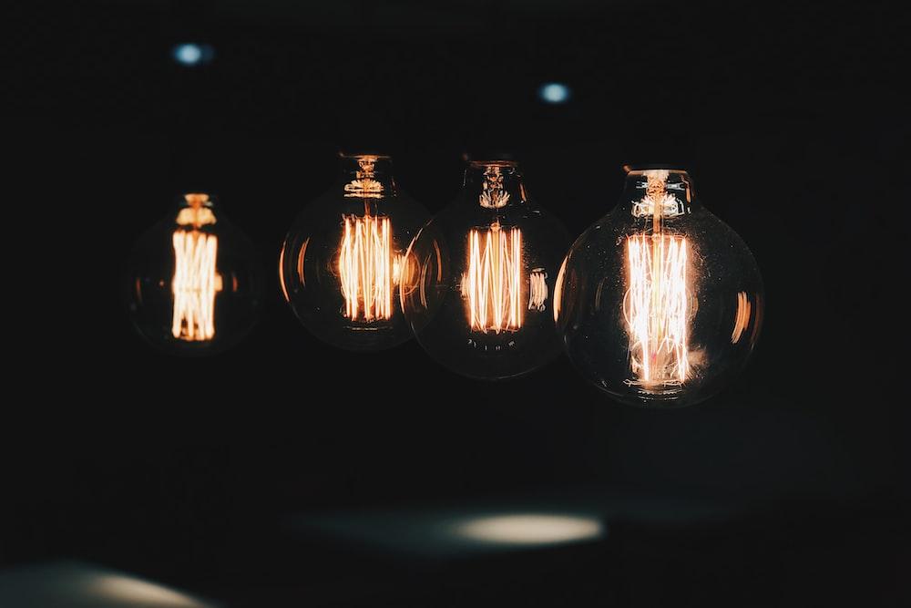 four lighted Edison light bulbs at the dark