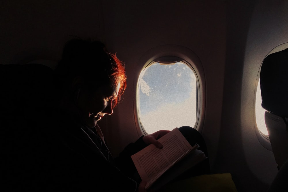 woman reading book in airplane