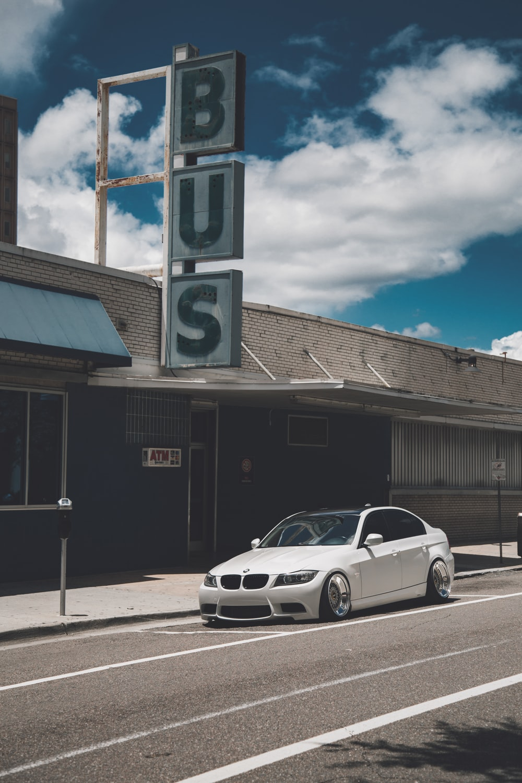 white BMW E90 sedan near Bus station